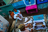 """Mayan peasants take care of dried-up bones of a deceased family member during the bone cleansing ritual at the cemetery in Pomuch, Mexico, 29 October 2019. Every year on the Day of the Dead, people of Pomuch, a small Mayan community in the south of Mexico, visit the cemetery to take part in a pre-Hispanic tradition of cleaning of bones of their departed relatives (""""Limpia de huesos""""). People who die in Pomuch are firstly buried for three years in an above-ground tomb then the dried-up bodies are taken out, bones are separated, wrapped in a decorated cloth, put into a wooden crate, and placed on display among flowers for veneration."""