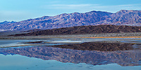 Death Valley has numerous mountain ranges.  After sunset, these blue and brown mountains reflect in a slow moving stream.
