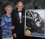 """Photo by Mike Ullery/National Aviation Hall of Fame.David Lee """"Tex"""" Hill and his wife Mazie pose beside """"Tex's"""" enshrinement poster prior to ceremonies in Dayton, Ohio. The former Flying Tiger was enshrined as part of the National Aviation Hall of Fame Class of 2006."""