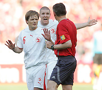 Johann Vogel (6) and Philippe Senderos (4) of Switzerland argues with referee Valentin Ivanov. France and Switzerland played to a 0-0 tie in their FIFA World Cup Group G match at the Gottlieb-Daimler-Stadion, Stuttgart , Germany, on Tuesday, June 13, 2006.