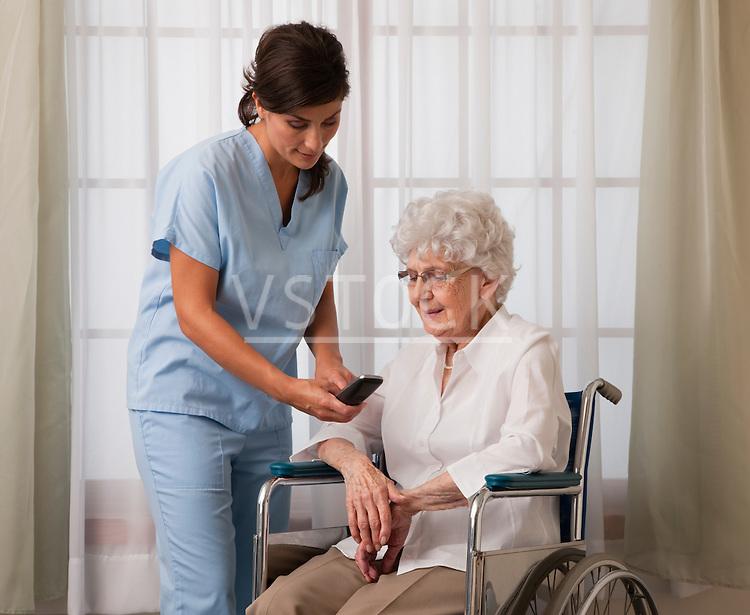 USA, Illinois, Metamora, Female nurse dialing phone for senior woman on wheelchair