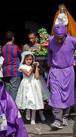 Antigua, Guatemala.  Semana Santa (Holy Week).  Young girls leaving the Cathedral of San Jose carrying an anda with the Virgin Mary.