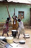 Kigoma, Tanzania. Girls pounding yams with pestle sticks in a wooden bowl.