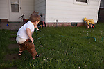 My sons, ages two and almost five, try to drink from the hose at the same time on a hot summer day. My older son is wearing his rain coat to protect himself from his squirt gun.