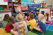 MR / Schenectady, NY. Zoller Elementary School (urban public school). Kindergarten inclusion classroom. Teacher reads big book to class group. The book highlights basic vocabulary words for early readers. MR: AM-gKw. ID: AM-gKw. © Ellen B. Senisi.