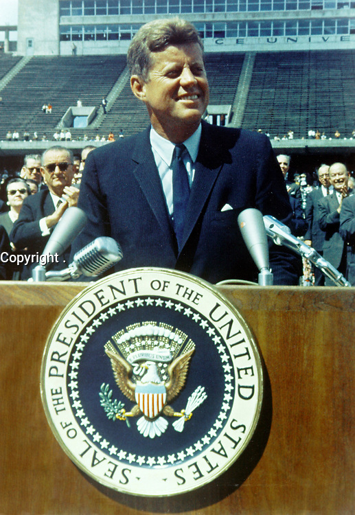 """Houston (TX) USA - 09/12/1962 - File Photo - President Kennedy speaks before a crowd of 35,000 people at Rice University in the football field. The following are excerpts from his speech. """" ...We set sail on his new sea because there is a new knowledge to be gained, and new rights to be won, and they must be won and used for the progress of all people. ...Whether it will become a force for good or ill depends on man, and only if the United States occupies a position of pre-eminence can we help decide whether this new ocean will be a sea of peace or a new terrifying theater of war. But I do say space can be explored and mastered without feeding the fires of war, without repeating the mistakes that man has made with extending his writ around this globe of ours. ...There is no strife, no prejudice, no national conflict in outer space as yet. Its conquest deserves the best of all mankind, and its opportunity for peaceful cooperation may never come again. But why, some say the Moon? Why choose this as our goal? And they may well ask, why climb the highest mountian? Why - 35 years ago - why fly the Atlantic? Why does Rice play Texas? We choose to go to the Moon, we choose to go to the Moon in this decade and do the other things, not because they are easy, but because they are hard, because that goal will serve to organize and measure the best of our energies and skills, because that challenge is one that we are willing to accept, one we are unwilling to postpone, and one in which we intend to win, and the others too."""""""