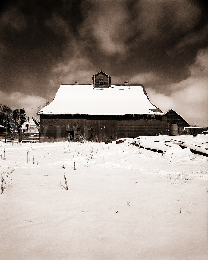 A barn covered with snow, a farmhouse in the distant background.