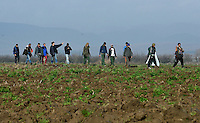 Pictured: Migrants walk in a field  Tuesday 01 March 2016<br /> Re: Thousands of migrants, still stranded at the Greek FYRO Macedonian border in Idomeni, Greece
