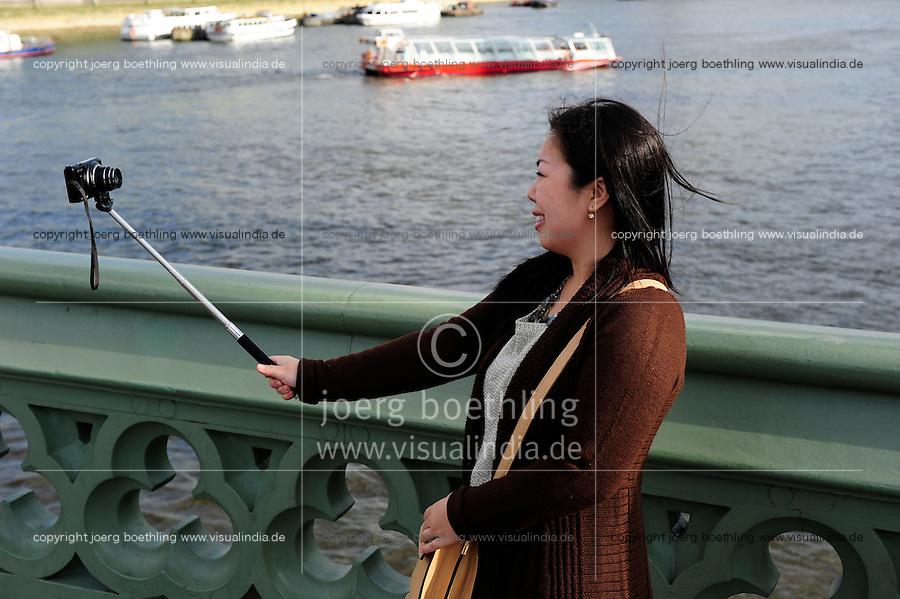 GREAT BRITAIN, London, asian tourist with selfie camera at river Thames / GROSSBRITANNIEN, London, asiatische Touristin mit Selfie Kamera an der Themse vor Big Ben