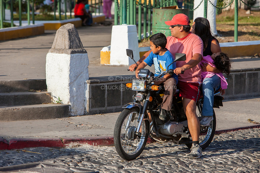 Antigua, Guatemala.  Father, Mother, and Two Children on Motorbike, no Helmet.