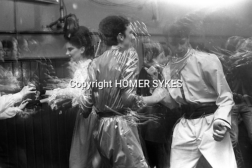 """Blitz Kids New Romantics at The Blitz Club Covent Garden, London, England 1980. Julia Fodor (Princess Julia) and a couple of """"Space Cadets"""" dancing the night away. <br /> <br /> Amelia Lonsdale writes in 2017. The Space Cadet is Dennis Sheldrick, he was in a band called Wonder Stories with fashion designer Keanan Duffty. He worked at the steel works in Scunthorpe, my mum (Yvonne Taylor) worked at Doncaster council. They were into art, my mum studied fashion at college but thats as far as it goes. They made most of their own clothes and would wear them out at places such as The Blitz but also at many more clubs up north. The woman dancing with him in what seems to be a matching outfit is called Denise King. <br /> The costume was an overall from his work that he customised, my mum made the cummerbund out of satin, mainly influenced by Bowie's Space Oddity and Kraftwerk. They were invited down to London to Billy's by Steve Strange and Rusty Egan when they were in the band Rich Kids and after that they would go once a month to London for one nighters."""