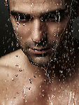 Thoughtful man face with his eyes down wet from shower water pouring on it, dramatic emotional portrait. Image © MaximImages, License at https://www.maximimages.com