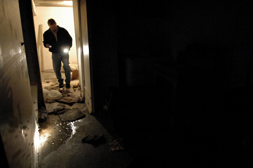 """""""This is one of the worst I've seen,"""" City of Regina bylaw standards officer Miles Kirkpatrick said after inspecting this rental property in North Central Regina. Here, Kirkpatrick tiptoes over sewage-soaked garbage in the home's basement. MARK TAYLOR GALLERY"""