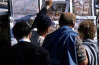 Group of tourist contemplate buying aquarelle paintings amongst street art, Montmartre, Paris, France.
