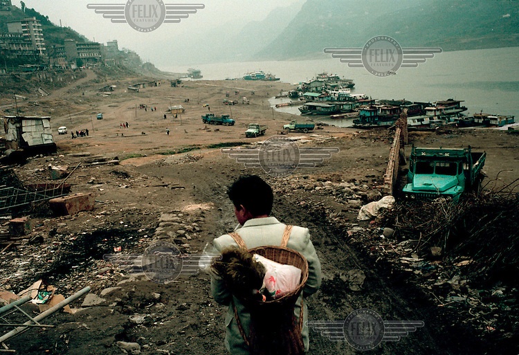 Migrant worker leaving Zigui after the town's recent demolition.  The purpose of dismantling buildings in the city is to clear an area which will eventually be submerged by the rising waters of the Yangtze river on the completion of the Three Gorges Dam project.