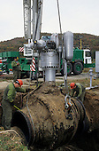 Slovakia: Workers using heavy lifting equipment to remove a main valve from a gas pipeline.
