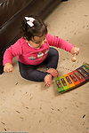 12 month old baby girl sitting on floor playing toy xylophone