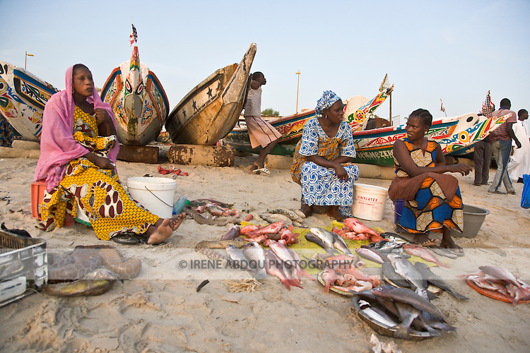 Three Fulani women in Dakar, Senegal sell fish at this beachside fish market, rows of colorfully painted fishing boats in the background.