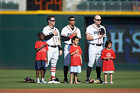 (L-R) Charlotte Knights outfielders Jake Elmore (3), Jacob May (8), and Mason Robbins (27) are joined by young fans on the field for the National Anthem prior to the game against the Durham Bulls at BB&T BallPark on July 4, 2018 in Charlotte, North Carolina. The Knights defeated the Bulls 4-2.  (Brian Westerholt/Four Seam Images)