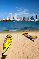 Kayaks on the beach and the downtown San Diego skyline as viewed from Coronado, San Diego, California