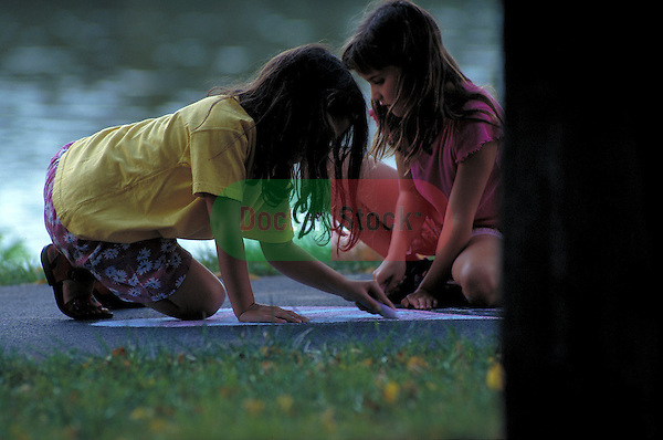 young girls drawing on sidewalk