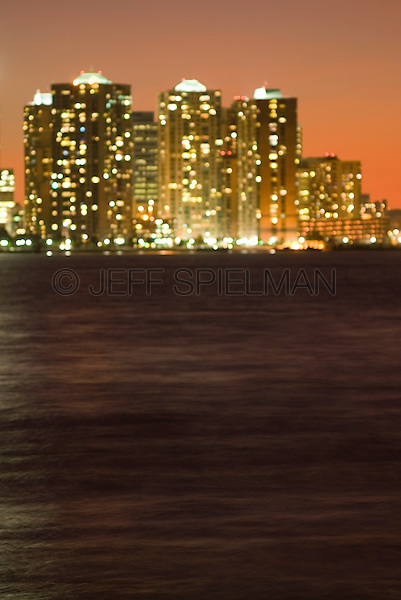 AVAILABLE FROM JEFF AS A FINE ART PRINT.<br /> <br /> AVAILABLE FROM PLAINPICTURE FOR COMMERCIAL AND EDITORIAL LICENSING.  Please go to www.plainpicture.com and search for image # p5690101.<br /> <br /> Modern Residental Apartment Buildings Illuminated at Dusk, Hudson River in the foreground, Defocused/Soft Focus Effect,  Jersey City, New Jersey, USA<br /> <br /> Viewed from Lower Manhattan Waterfront