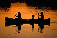 Silhouette of people paddling a canoe at sunset.