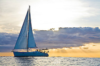 Cruising sailboat at sunset off the west coast of Oahu, Hawaii