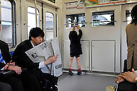A boy taking a photo of the train driver in Tokyo, Japan.<br />