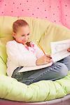 USA, Illinois, Metamora, Girl (10-11) sitting on soft chair and writing
