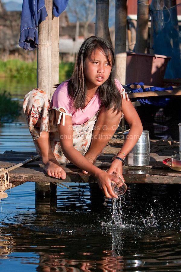 Myanmar, Burma.  Girl Washing Glass in Lake Water, Inle Lake, Shan State.