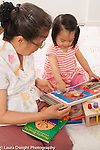 18 month old toddler girl with grandmother pointing to illustration in book she is reading