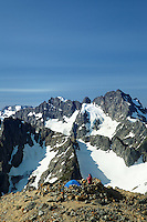 Woman at high alpine backcountry campsite on Sahale Arm, Washington's North Cascade Mountains in background, North Cascades National Park, Washington State, USA
