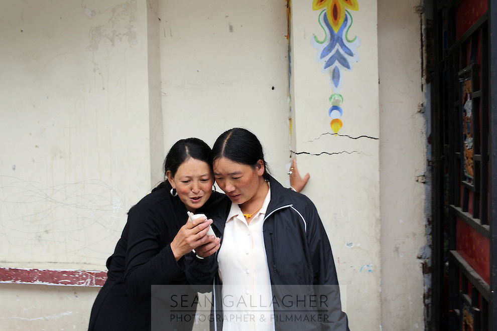 Tibetan woman looking at a cellphone in the town of Heishui on the south-east edge of the Tibetan Plateau in Sichuan Province, western China.