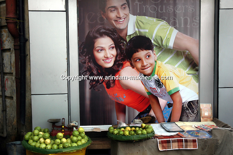 A fruit stall in front of an advertisement at Newmarket area in Kolkata. Street food stalls are serving the office goers for decades. All kind of Indian foods are available on the street at an affordable price. They sale them openly. Street food stalls are another results of unempoloyment and over poppulation. They serve millions of people in India. Kolkata, West Bengal,  India  7/18/2007.  Arindam Mukherjee/Landov