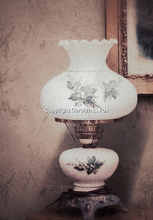 An antique lamp sits on a old table.  A portion of an old picture can be seen in the background.