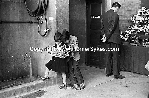 Victoria, London. 1968<br /> Engrossed in The Hotspur comic, sibling brothers in their best out of prep school clothes. They are wearing Clarks sandals, a blue gabardine mackintosh, and a tweed jacket with pocket handkerchief, with short and long grey trousers. They show no interest in the display that their father admires at the Royal Horticultural Society Annual Flower Show.