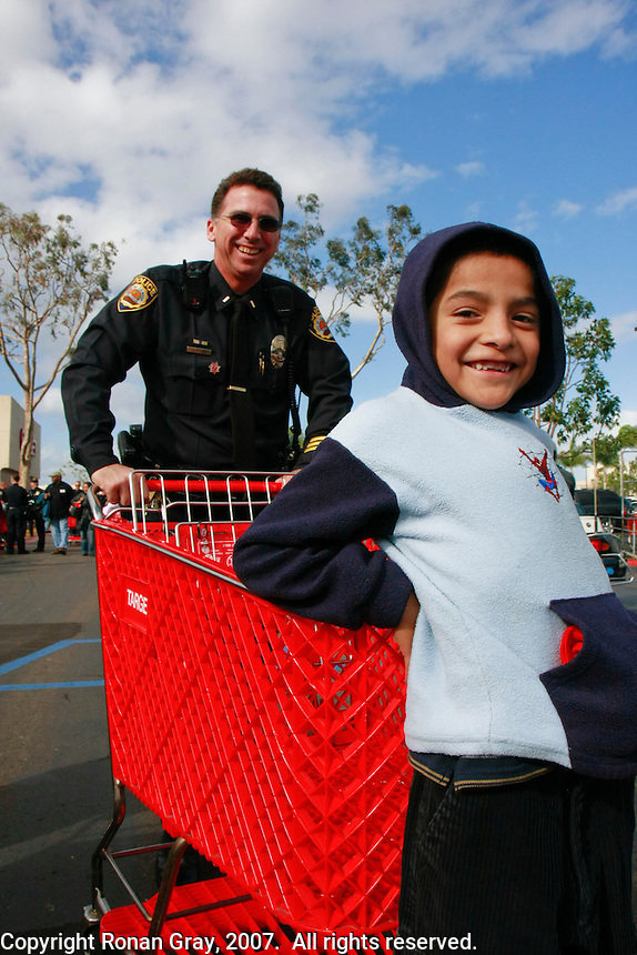 A San Diego Police Officer pushes a young boy on a shopping cart towards the Sports Arena Target store in San Diego for the annual Shop-with-a-Cop event on December 1, 2007.  Three hundred disadvantaged children were bused to Sea World early on Saturday morning where they were paired up with a police officer for the event.  After breakfast they drove to the store in a convoy of more than three hundred police vehicles with sirens blaring, lights flashing and Santa waving from a police helicopter hovering above them.  Each child had a $100 gift card to spend and many choose to buy clothes, for themselves, their siblings or parents instead of toys.