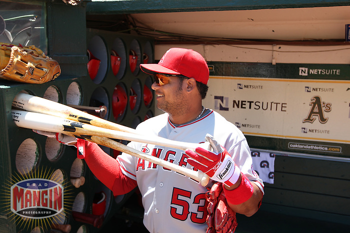 OAKLAND, CA - JULY 19:  Bobby Abreu #53 of the Los Angeles Angels of Anaheim puts his bats in the bat rack in the dugout before the game against the Oakland Athletics at the Oakland-Alameda County Coliseum on July 19, 2009 in Oakland, California. Photo by Brad Mangin