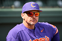 A bright, sunny day is reflected in the sunglasses of head coach Monte Lee (18) of the Clemson Tigers before the start of the Reedy River Rivalry game against the South Carolina Gamecocks on Saturday, March 2, 2019, at Fluor Field at the West End in Greenville, South Carolina. Clemson won, 11-5. (Tom Priddy/Four Seam Images)