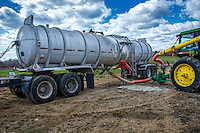 A worker opens a valve on a tanker truck filled with lime from a water treatment plant that is speed on parts of the Bran Farm property.