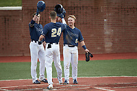 Ricky Clark (24) of the Wingate Bulldogs is congratulated at home plate by teammates McCann Mellett (9) and Hunter Dula (17) after hitting a home run against the Concord Mountain Lions at Ron Christopher Stadium on February 1, 2020 in Wingate, North Carolina. The Bulldogs defeated the Mountain Lions 8-0 in game one of a doubleheader. (Brian Westerholt/Four Seam Images)