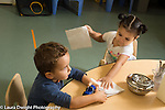 Education Preschool Child care two year old program girl passing out napkin to classmate at mealtime