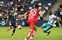 KANSAS CITY, KS - AUGUST 10: Andres Mosquera #4 of Club Leon FC attempts to stop Ozzie Cisneros #25 of Sporting Kansas City as he shoots on goal in the second half during a game between Club Leon FC and Sporting KC at Children's Mercy Park on August 10, 2021 in Kansas City, Kansas.