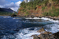 Rocky cliffs on the shore with Yasur Volcano visible in the background, Tanna Island, Vanuatu.