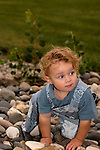 A TODDLER CREEPS ACROSS THE RIVER STONES