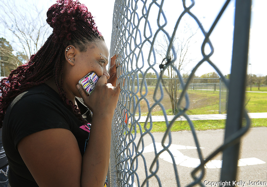 Kelly.Jordan@jacksonville.com--030812--Anitra Stokes, anxiously waits at the fence for news about her son, a 7th grader at Yulee Middle School, after the school was put on lockdown following reports of a gun on campus Thursday morning, March 8, 2012. Nassau County Sheriff's Officers responded to the school locked it down and searched the school and found no weapons. There were tense moments for many parents as they gathered outside of the school for information and to pick up their children.(The Florida Times-Union, Kelly Jordan)