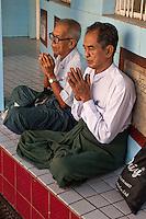 Myanmar, Burma, Yangon.  Sule Pagoda.  Two Men in Early-Morning Prayers.