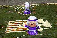 Antigua, Guatemala.  Cucuruchos Dolls decorate an alfombra (carpet) of  pine needles and other traditional materials in a street in advance of the passage of a procession during Holy Week, La Semana Santa.