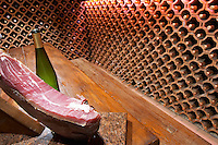 The wine cellar and tasting room where the walls are lined with bottles stacked piled in terracotta earthenware tubes.. Wine glasses on the table and a dry cured dried ham on a cutting stand. Vinarija Stankela Stanko winery, Medugorje, near Mostar. Medjugorje. Federation Bosne i Hercegovine. Bosnia Herzegovina, Europe.